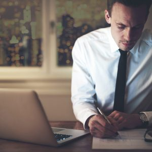 Accountant working at office at night signing document, working late overtime